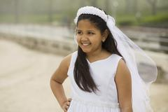 Hispanic girl wearing first communion gown and veil Stock Photos