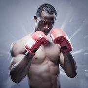 Back lit African boxer with arms raised Stock Photos