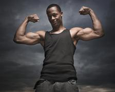 African man flexing arms, storm clouds in distance Stock Photos