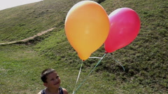 Young boy lets balloons go into sky, slow motion Stock Footage