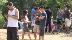 Young people playing Pokemon go game in city park Stock Footage