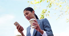Woman sipping coffee outside and using smartphone Stock Footage