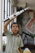 Mixed race boy playing with model rocket Stock Photos