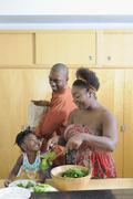 Black family preparing salad in kitchen Stock Photos