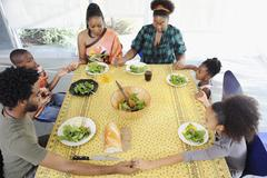Black family saying grace at dining room table Stock Photos