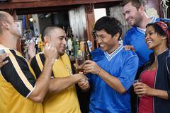 Happy men shaking hands in sports bar Stock Photos