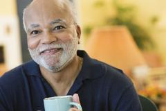 Smiling African American man drinking coffee Stock Photos