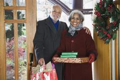 African American couple arriving with Christmas gifts Stock Photos