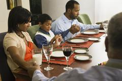 African American family saying grace at dining table Kuvituskuvat