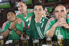 Worried men watching television in sports bar Stock Photos