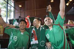 Cheering Hispanic men watching television in sports bar Stock Photos