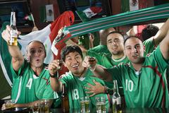Cheering men drinking in sports bar Stock Photos