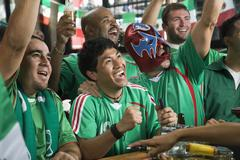 Cheering men watching television in sports bar Stock Photos