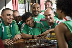 Happy men drinking shots in sports bar Stock Photos