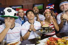 Sports fans drinking and eating in sports bar Stock Photos