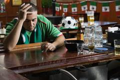 Unhappy man drinking in sports bar Stock Photos
