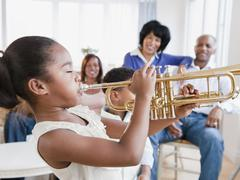 African American family watching daughter play trumpet Stock Photos
