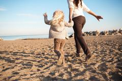 BACK VIEW: Little daughter runs with his mother on a beach Stock Photos