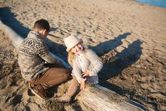 Little brother and sister sit on a old beam on a beach Stock Photos