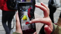 """People playing """"Pokemon GO"""" the hit augmented reality smart phone app - stock footage"""