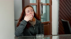 Girl in Outdoor Cafe Draws on Cigarette and Sneezes Due to Cigarette Smoke Arkistovideo