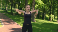 Fitness woman warm up shoulders outdoor. Fit girl stretching in green park Stock Footage