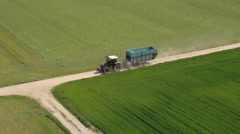 AERIAL: Agricultural tractor with loader driving between vast lush meadow fields Stock Footage