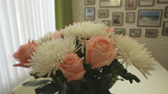 Beautiful bouquet of white chrysanthemum and pink roses in home interior - stock footage