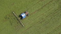 AERIAL: Flying above tractor turning mowed hay with rakes on farmland field Stock Footage