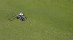 AERIAL: Flying above tractor driving on farmland field, drying mowed hay Stock Footage