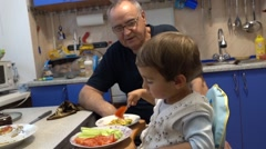 Small boy shares his meal with his granddad - stock footage