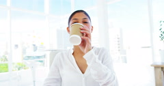 Smiling woman sipping coffee in office Stock Footage