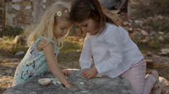 Two children playing with shells - stock footage