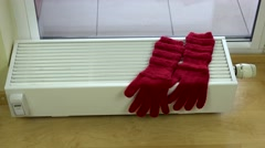 Girl hand put red woolen gloves on radiator at home Stock Footage