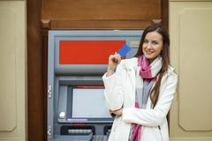 Young happy brunette woman withdrawing money from credit card at ATM Stock Photos