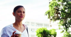 Woman sipping coffee on street Stock Footage