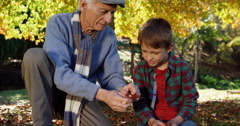 Grandfather and grandson playing with leaves Stock Footage