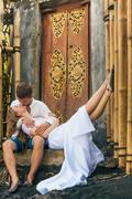 Happy family enjoying romantic honeymoon holiday on black sand beach Stock Photos
