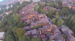 Aerial: Suburb, houses and buildings surrounded by trees and greenery Stock Footage