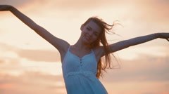 She rejoices at sunset and the wind blows Stock Footage