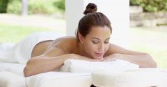Naked woman on massage table smiles as she rests - stock footage