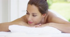 Woman smiles and relaxes on massage table - stock footage