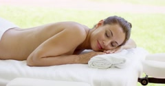 Woman relaxing on spa table on outdoor patio - stock footage