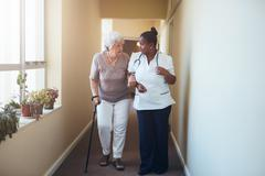 Senior woman with walking stick being helped by a female nurse a Stock Photos