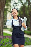 Happy busy business woman walking while talking on a smart phone Stock Photos