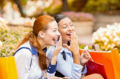two laughing happy looking girls discussing latest gossip news - stock photo