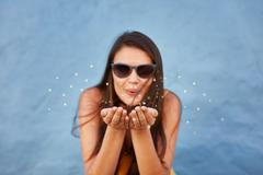 Young woman blowing sparkles Stock Photos