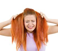 Stressed woman pullling her hair out - stock photo