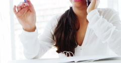Woman calling on smartphone holding pen Stock Footage