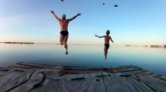 Peopie jumps off a wooden dock into the water . Slow motion Stock Footage